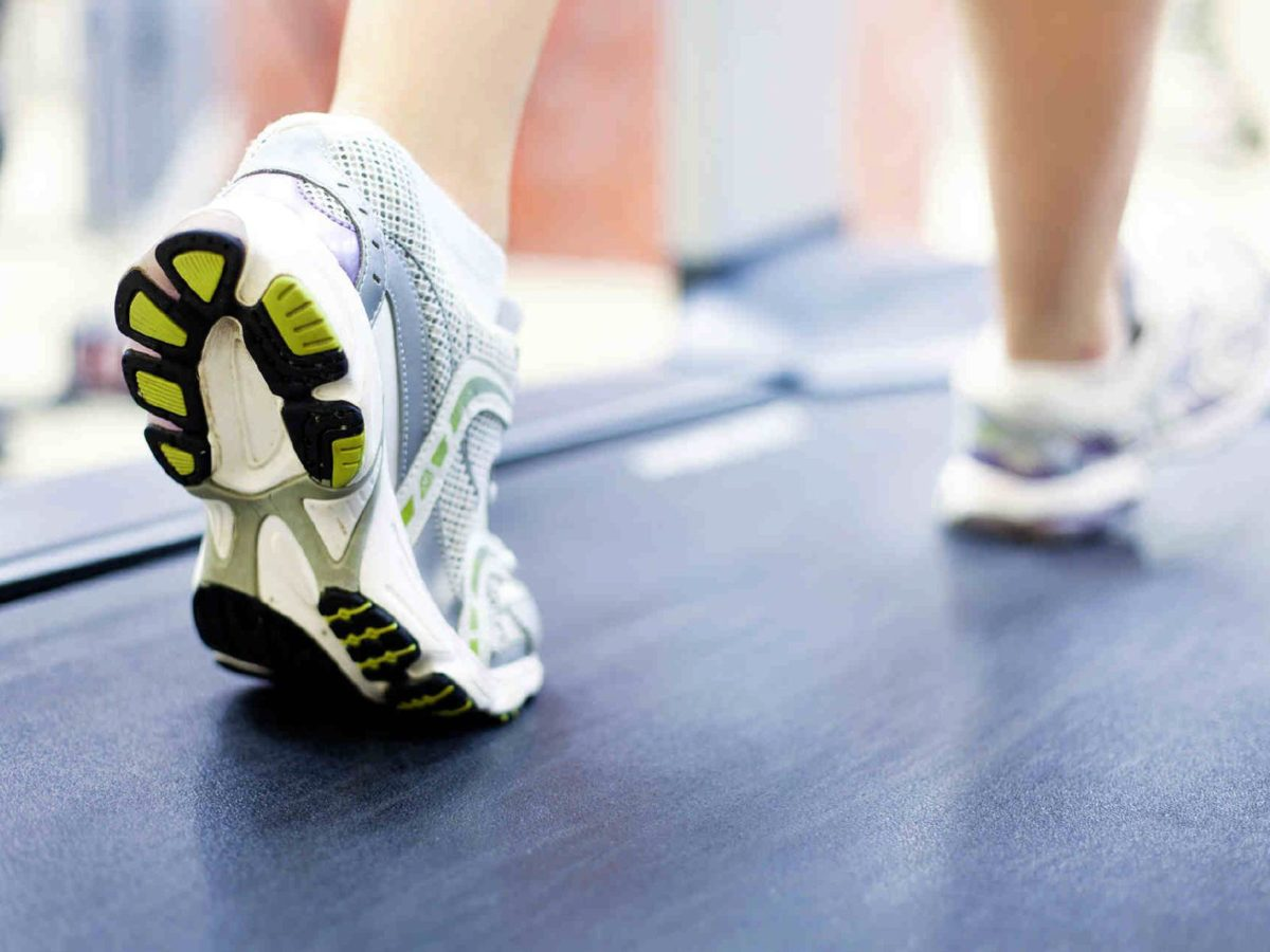 The image shows a person walking on the treadmill.